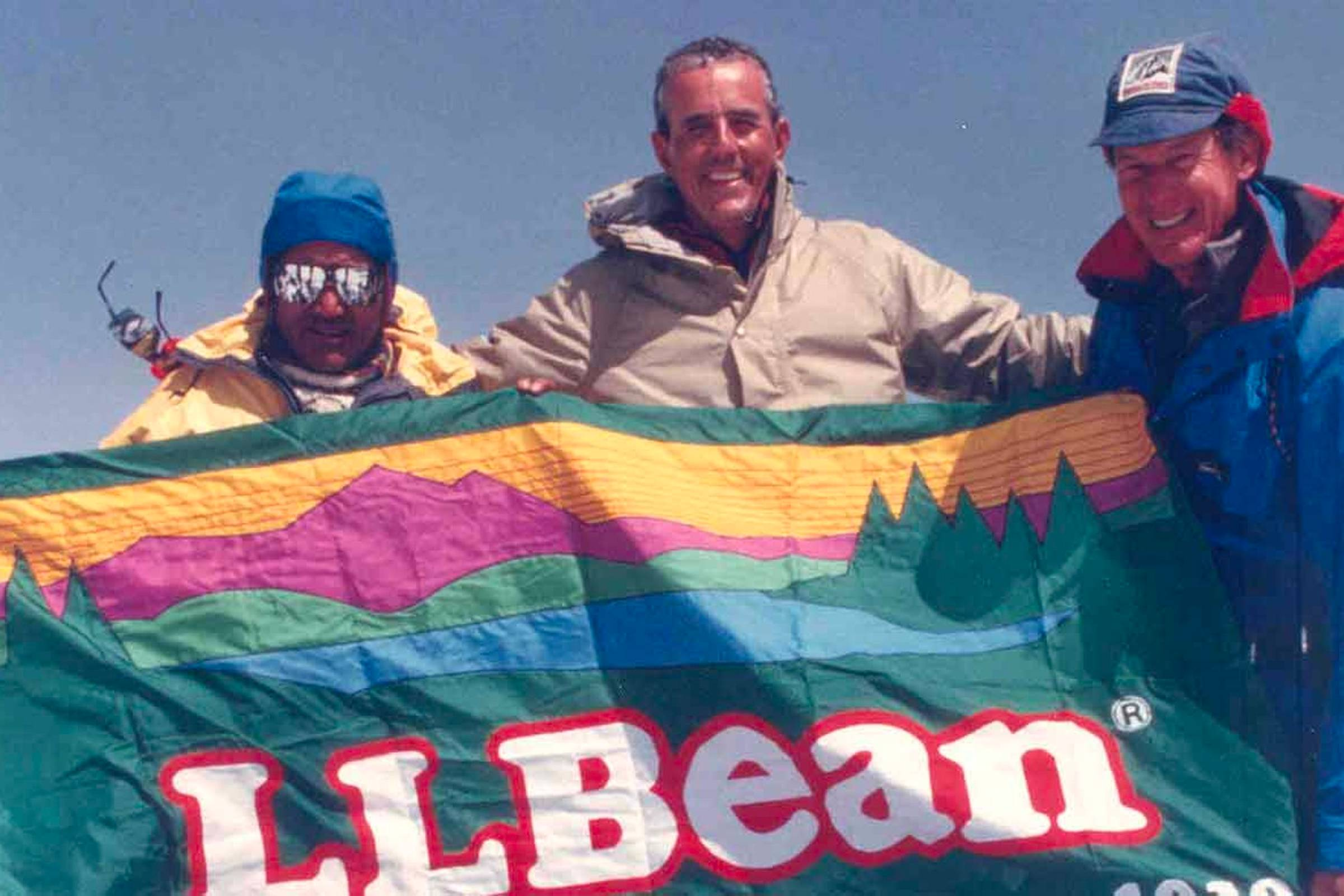 "Former L.L. Bean President Leon Gorman holding a ""Sunrise Over Katahdin"" logo flag with climbers training for the Everest Peace Climb in 1990. L.L. Bean outfitted the climb"